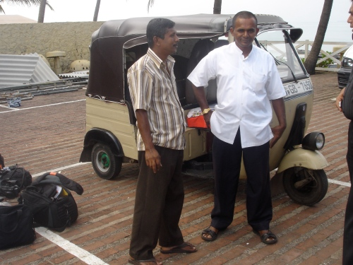 Nimal, on the right, stands in front of his trishaw